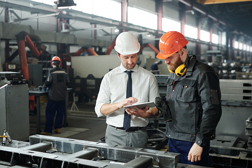 Young master in hardhat and bearded engineer discussing technical sketch 1207928621