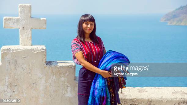 young mayan woman carrying woven patterned tablecloths for sale at shore of lake atitlan guatemala - guatemala fotografías e imágenes de stock
