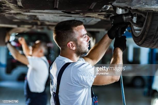 ワークショップで車のタイヤを交換する若いメカニック。 - 交代 ストックフォトと画像