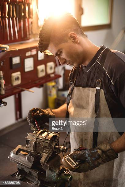 young mechanic examining electric motor with voltmeter in a workshop. - electric motor stock photos and pictures