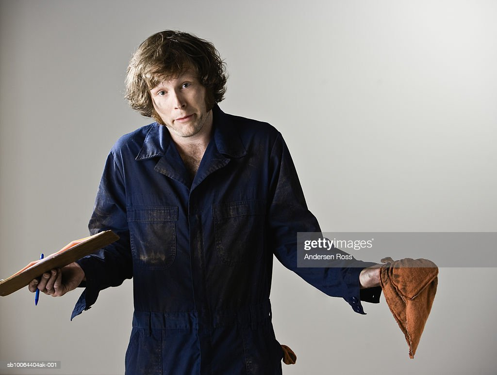 Young mechanic holding clipboard and rug, standing in studio, portrait : Stock Photo
