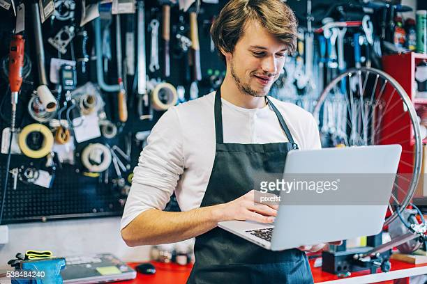Young mechanic with laptop
