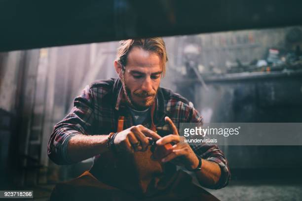 young mechanic working and using tools in workshop - blacksmith shop stock photos and pictures