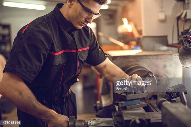 Junge Mechaniker Arbeiten auf Drehmaschine Maschine in der Werkstatt.