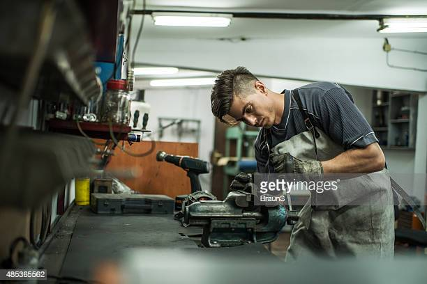 Young mechanic working on vice grip at workshop.