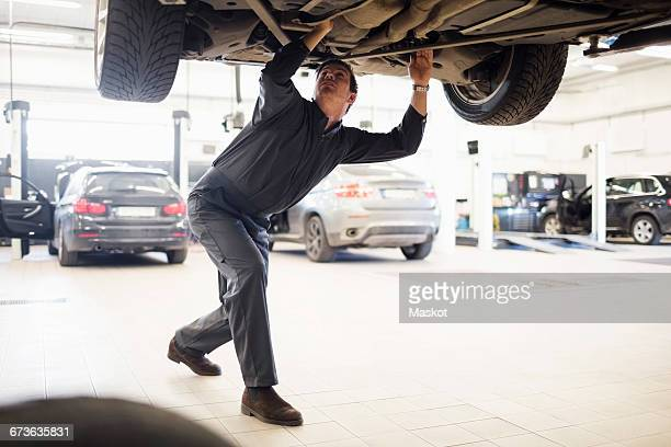 Young mechanic working under car in repair shop