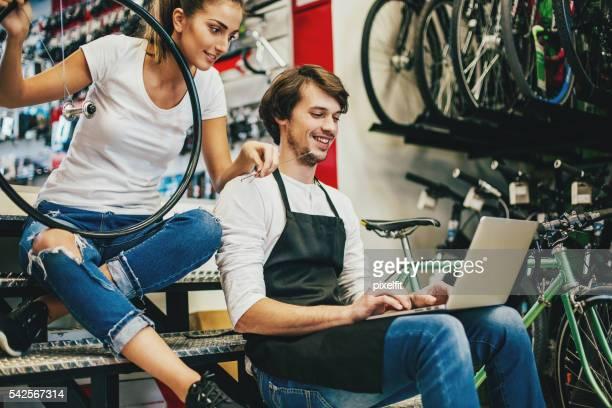 Junge Mechaniker mit Laptop in einem Fahrrad shop