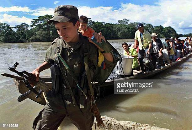 A young member of the Revolutionary Armed Forces of Colombia pulls a barge of supporters ashore 27 June 2001 in the tiny rebelheld town of La...