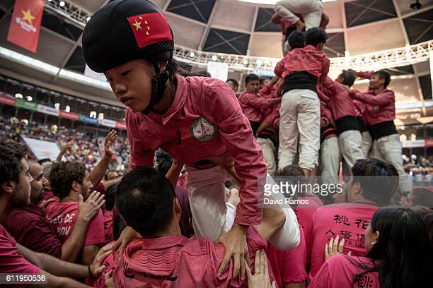 A young member 'Xiquets de Hanghzou' in action after building a human tower during the 26th Tarragona Competition on October 1 2016 in Tarragona...