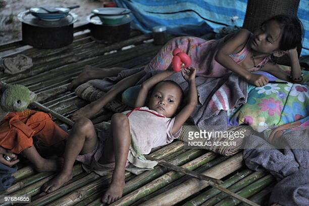 Young members of a Karen refugee family sit under a temporary shelter on the ThaiMyanmar border at the Safe Haven orphanage over 100 kms north of Mae...