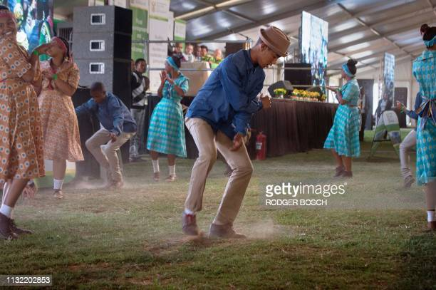 Young members of the community perform a traditional Khoi/San 'Riel' Dance which includes kicking up dust at a public meeting where the South African...