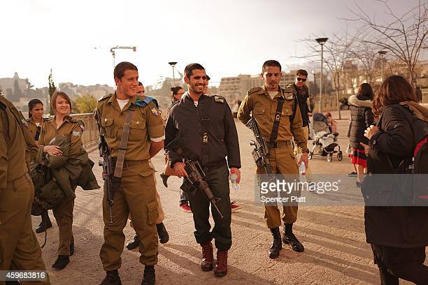Young members of the Israeli Defense Forces pause in a park near the Old City on November 28 2014 in Jerusalem Israel Nine Israelis have been killed...