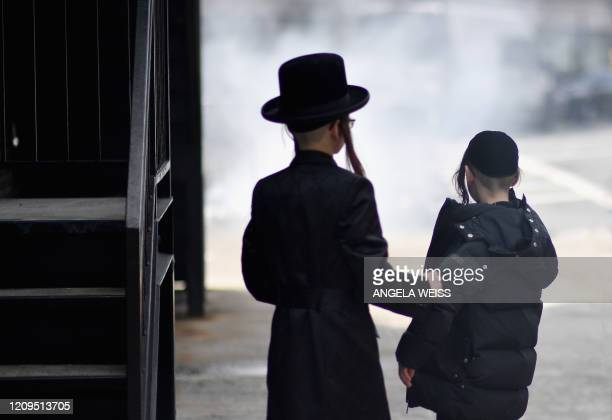 Young members of the Orthodox Jewish community look at smoke from an extinguished fire on April 8 2020 in Brooklyn New York as the Passover holiday...