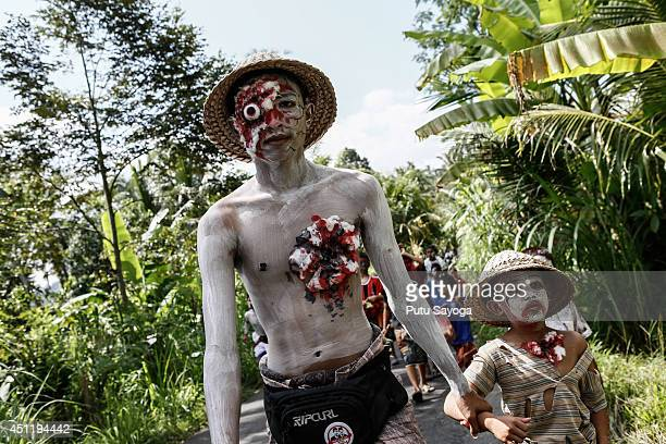 Young members of the village community walk around their village with painted bodies during the Grebeg Ritual on June 25 2014 in Tegallalang Village...