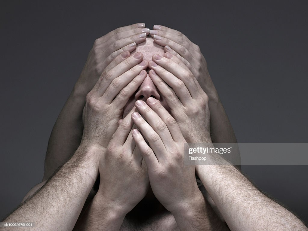 Young men and woman covering face, close-up : Stock Photo