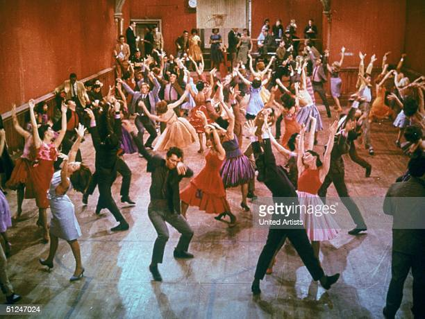 1961 Young men and women dance with their arms thrust into the air inside a gymnasium during a musical number from the film 'West Side Story'...