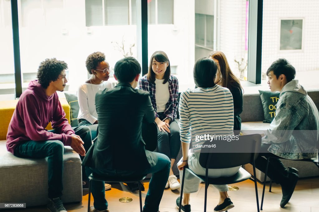 Young men and women discussing at the cafe. : Stock Photo