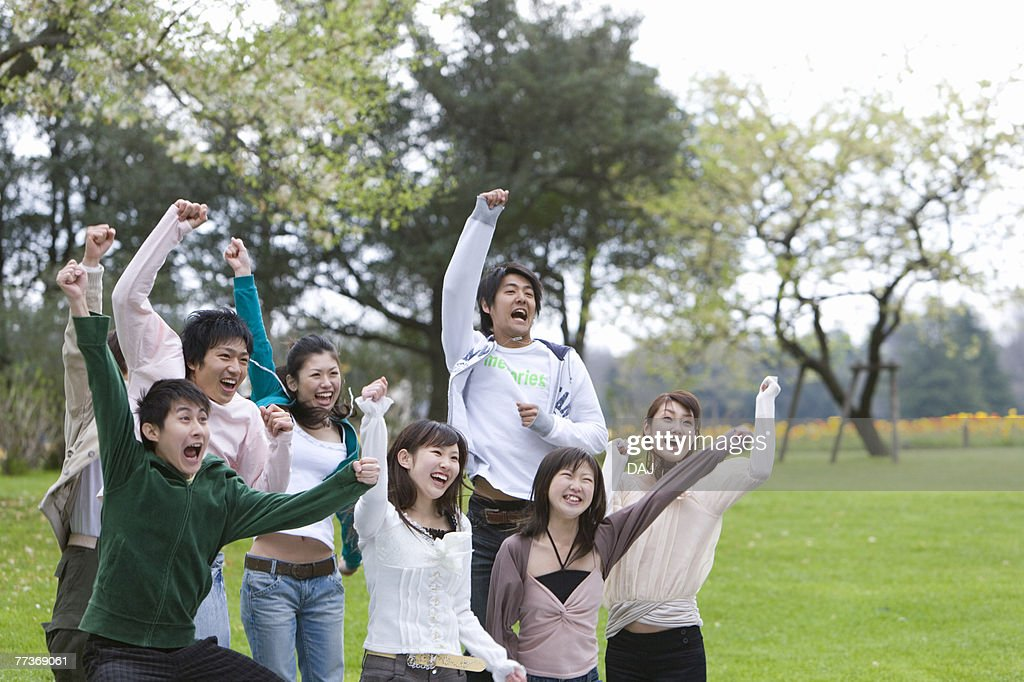 Young Men and Women Holding Fists in the Air, Side View : Stock Photo