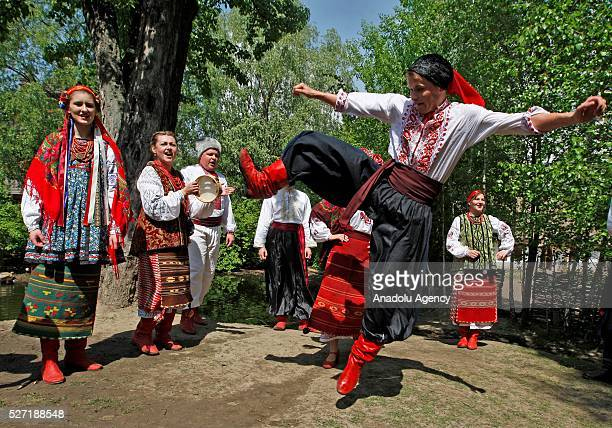 Young men and women in Ukrainian traditional clothes dance during folk Easter Tradition of pouring water called Pouring Monday in open air Cossack...