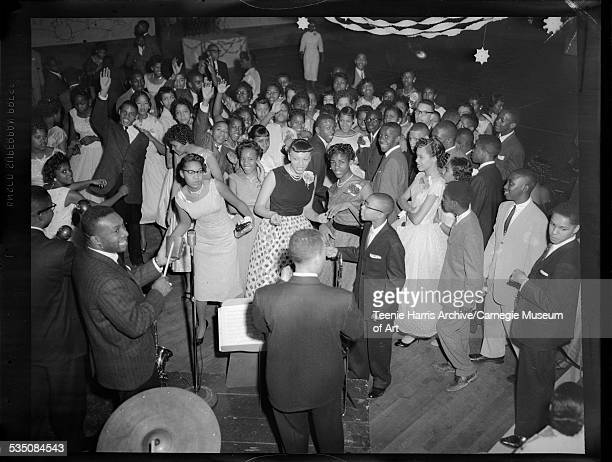 Young men and women including Barbara Payne wearing dark sleeveless top dancing to Walt Harper's band with Walt Harper playing cowbell in gymnasium...