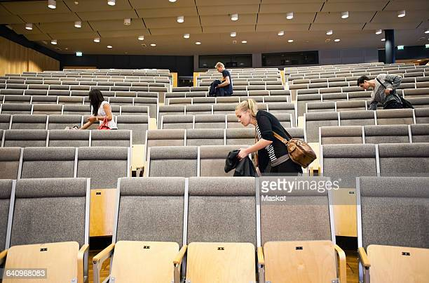 Young men and women leaving auditorium after seminar