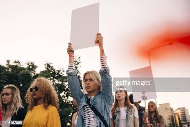young men and women protesting with posters while marching in city against sky - demonstrant stock-fotos und bilder