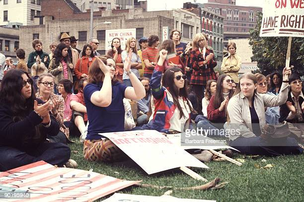 Young men and women sit and gather at a park while holding a sign that reads 'Our Right To Decide' at a reproductive rights demonstration Pittsburgh...