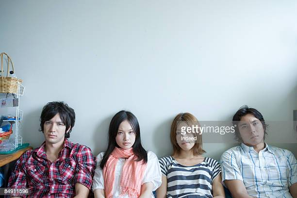 Young men and women sitting on side by side