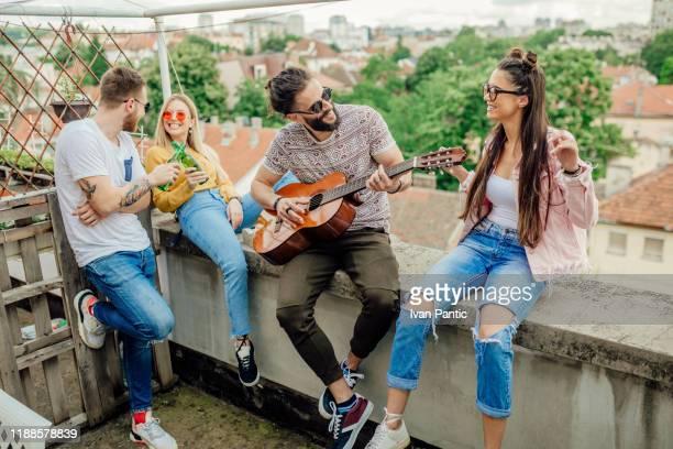 jonge mannen en vrouwen zittend op de top van het dak, plezier - eenmalig evenement stockfoto's en -beelden