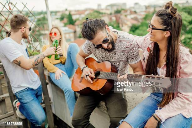 young men and women sitting on top of the roof, having fun - gara sportiva individuale foto e immagini stock