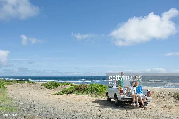 Young men and women sitting on truck at beach