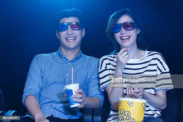 Young men and women watching movies in the cinema