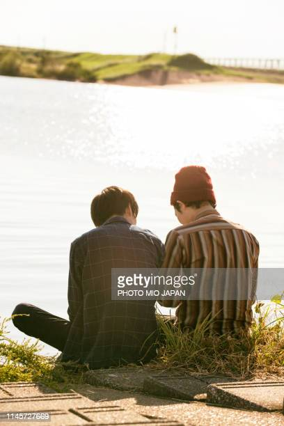 young men are enjoying the time staying beside the river. - 静かな情景 ストックフォトと画像
