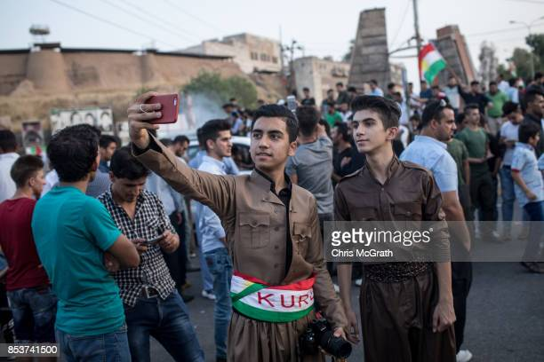 Young men are seen taking a selfie on the street as people celebrate taking part in the Kurdistan independence vote on September 25 2017 in Kirkuk...