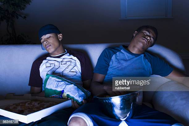 Young men asleep in front of the TV