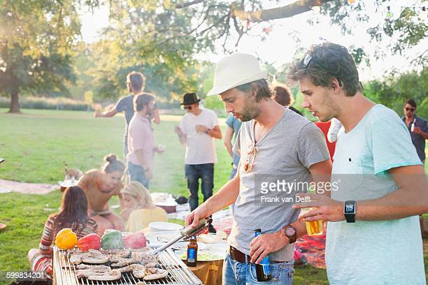 Young men barbecuing at group party in park