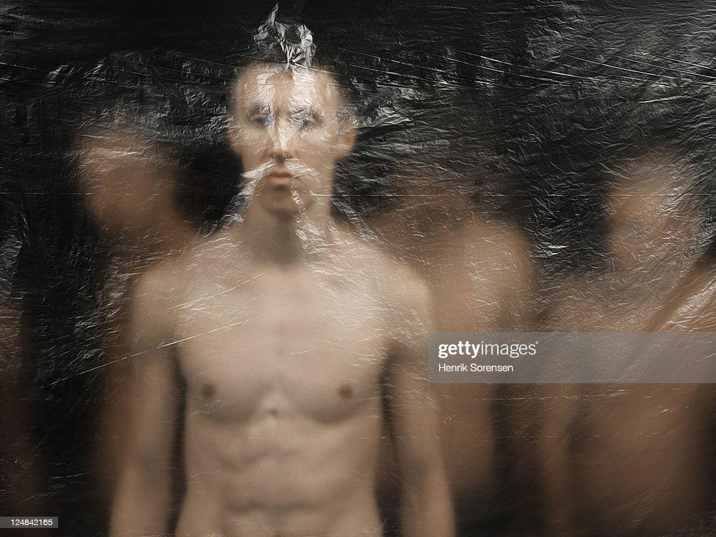 young men behind plastic screen : Stock Photo