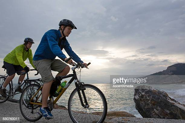 young men bike along sea wall, above crashing surf - retaining wall stock pictures, royalty-free photos & images