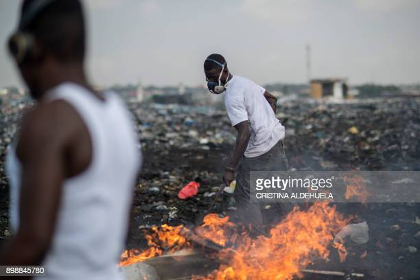 TOPSHOT Young men burn ewaste at Agbogbloshie dumpsite in Accra on November 29 2017 The dumpsite is located in Agbogbloshie slum a former wetland in...