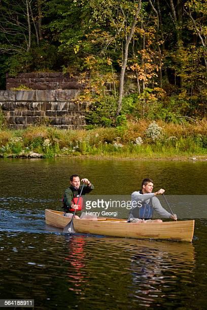 2 young men canoe on Farmington River, Collinsville, Connecticut, USA.