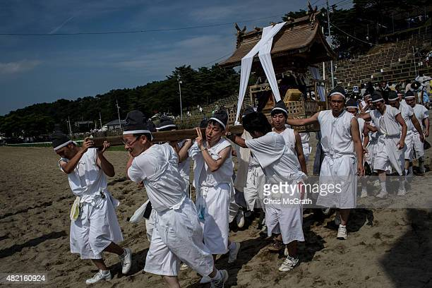 Young men carry a portable shrine across the race track during the Soma Nomaoi festival at Hibarigahara field on July 26 2015 in Minamisoma Japan...