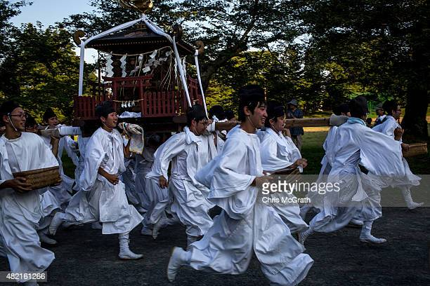 Young men carry a portable shrine to the Nakamura Shrine after the days racing during the Soma Nomaoi festival at Hibarigahara field on July 26 2015...