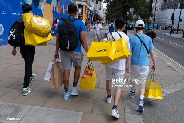 Young Men carry their yellow Selfridges shopping bags purchases on Oxford Street in the West End on Covid 'Freedom Day'. This date is what Prime...