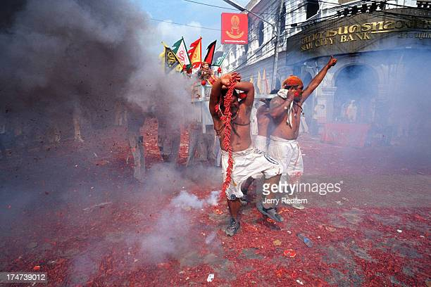 Young men carrying a sedan chair holding a temple deity dance amid clouds of firecracker smoke while parading in the streets of Phuket town during...