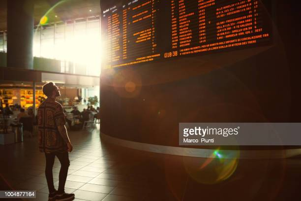 young men checking his train in time board - arrival stock pictures, royalty-free photos & images