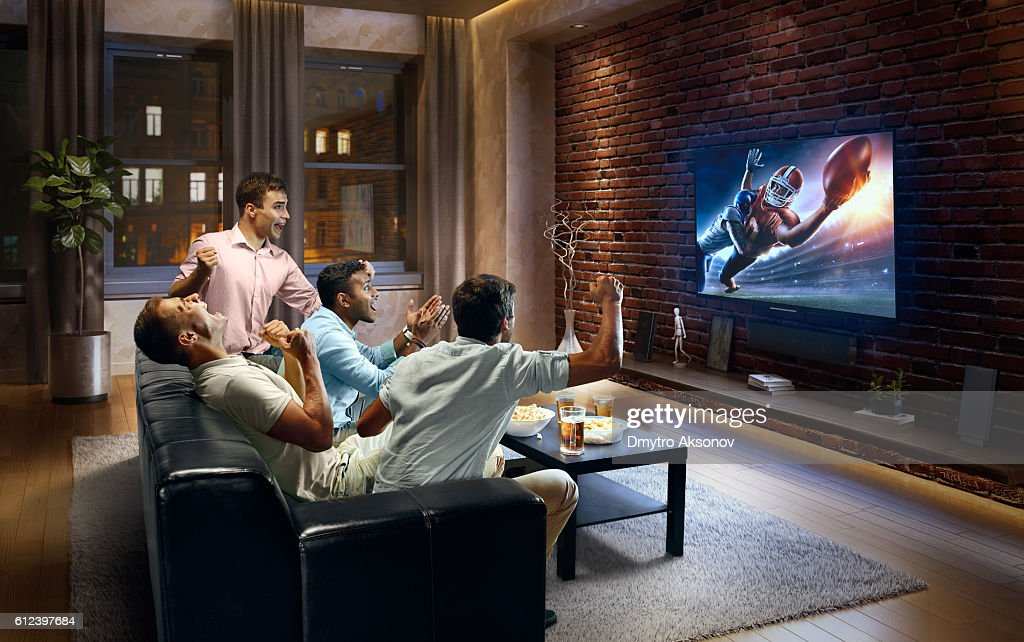 Young men cheering and watching American football game on TV : Stock Photo