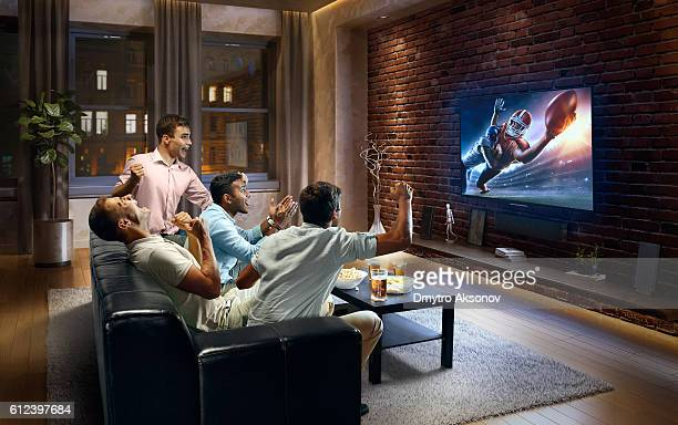 young men cheering and watching american football game on tv - guardare con attenzione foto e immagini stock