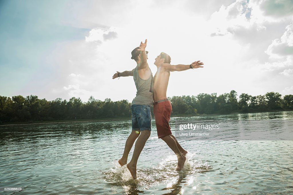 Young men chest bumping in lake : Stock Photo