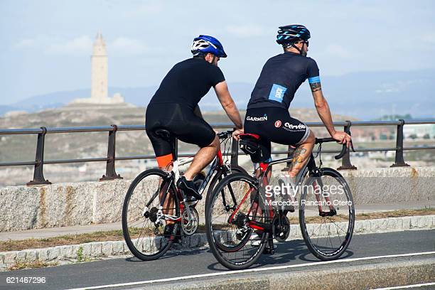 young men cycling in front of 'torre de hercules'. - a coruña stock pictures, royalty-free photos & images