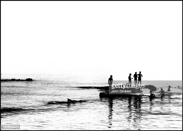 Young men diving into the Mediterranean Sea off the coast of Turkey from rocks.